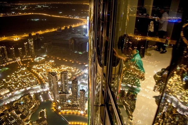 Dizzy heights: a child exploring the night landscape of the city of Dubai from the Burj Khalifa